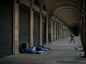 Homeless people sleep on a square where restaurants are closed due to sharpest resurgences of coronavirus in Barcelona, Spain (Emilio Morenatti/AP)