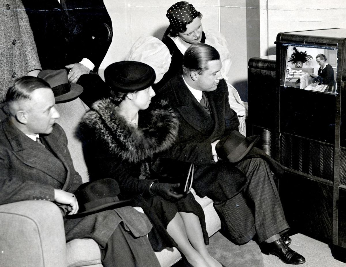 A group watching an early television at the 1937 Ideal Home Exhibition at Olympia.