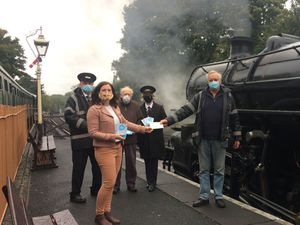 Chairman of Bridgnorth Art Trail, Councillor Julia Buckley, hands a £100 donation to Severn Valley Railway station master Chris Thomas
