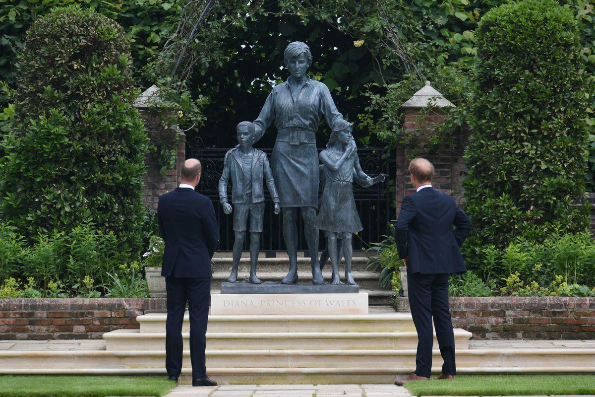 The Duke of Cambridge (left) and Duke of Sussex look at a statue they commissioned of their mother Diana, Princess of Wales, in the Sunken Garden at Kensington Palace, London, on what would have been her 60th birthday.