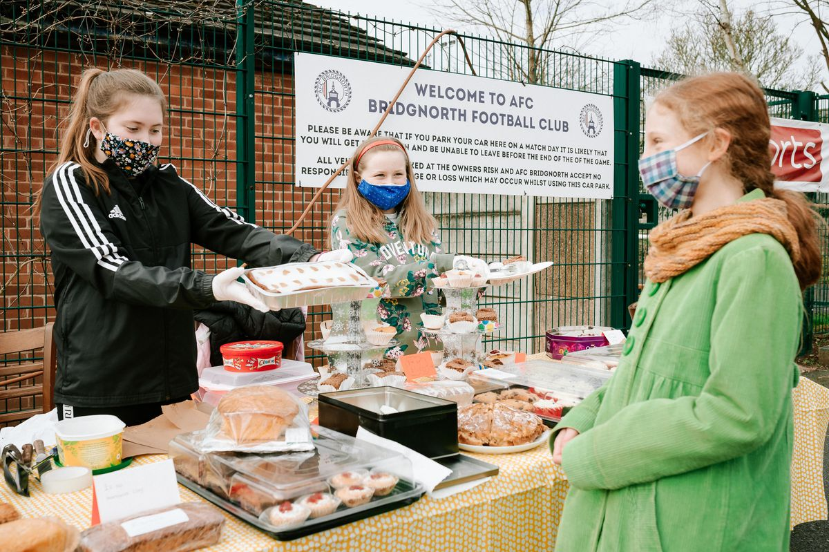 Neve Cramm, 12, and Annabel Buckley, 11, serve Merab Walker, 11, to raise funds