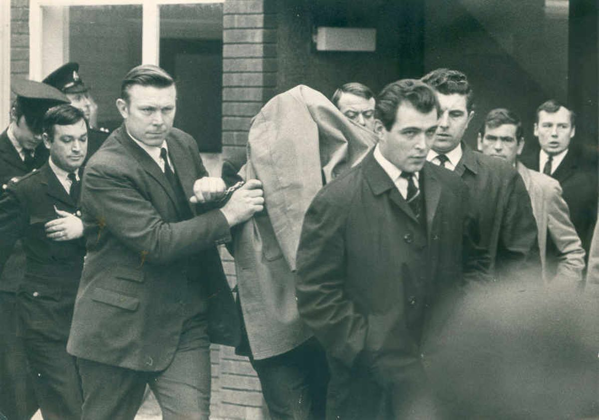 Raymond Morris hides under a coat as he is led into court