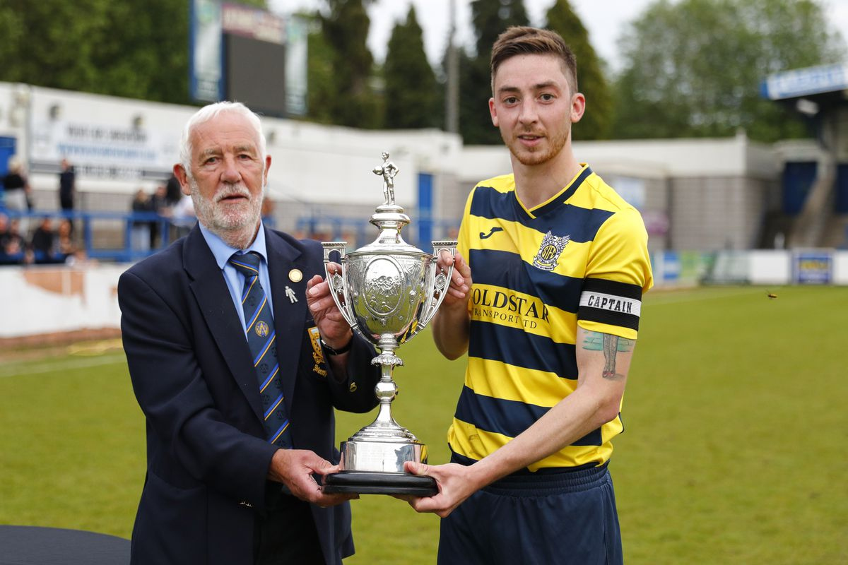 Shifnal Town captain Ben Perks is presented with the Shropshire Senior Cup by Dave Ralphs from the Shropshire FA Pic: James Baylis