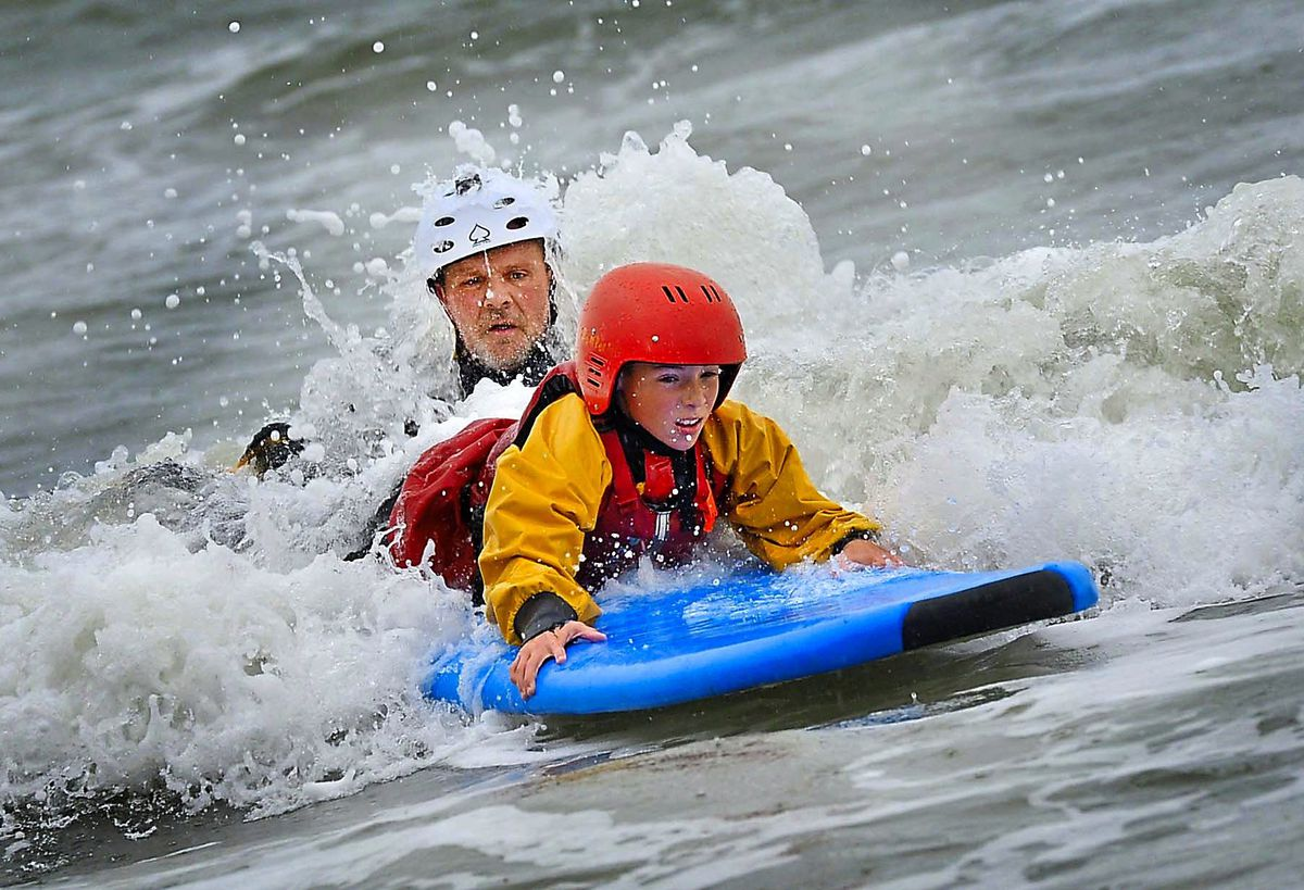 Outdoor educator Matty Bowman surfing with pupils from John Randall Primary School