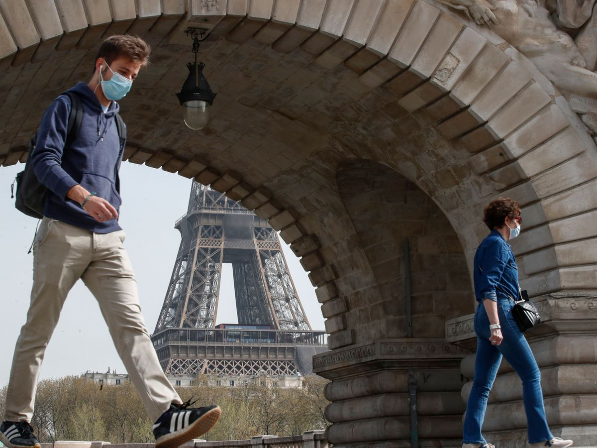 People wearing masks to prevent the spread of Covid-19 cross the Bir Hakeim bridge in Paris (Michel Euler/PA)