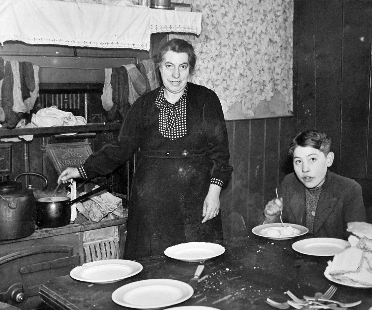 Madame Hoorne in the kitchen of the cottage on a Chesterton farm in 1941 with her son Gerard