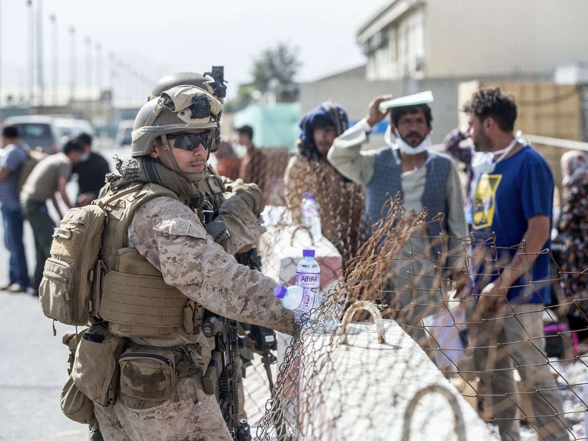 Marines with Special Purpose Marine Air-Ground Task Force-Crisis Response-Central Command (SPMAGTF-CR-CC) provide assistance during an evacuation at Hamid Karzai International Airport in Kabul, Afghanistan.