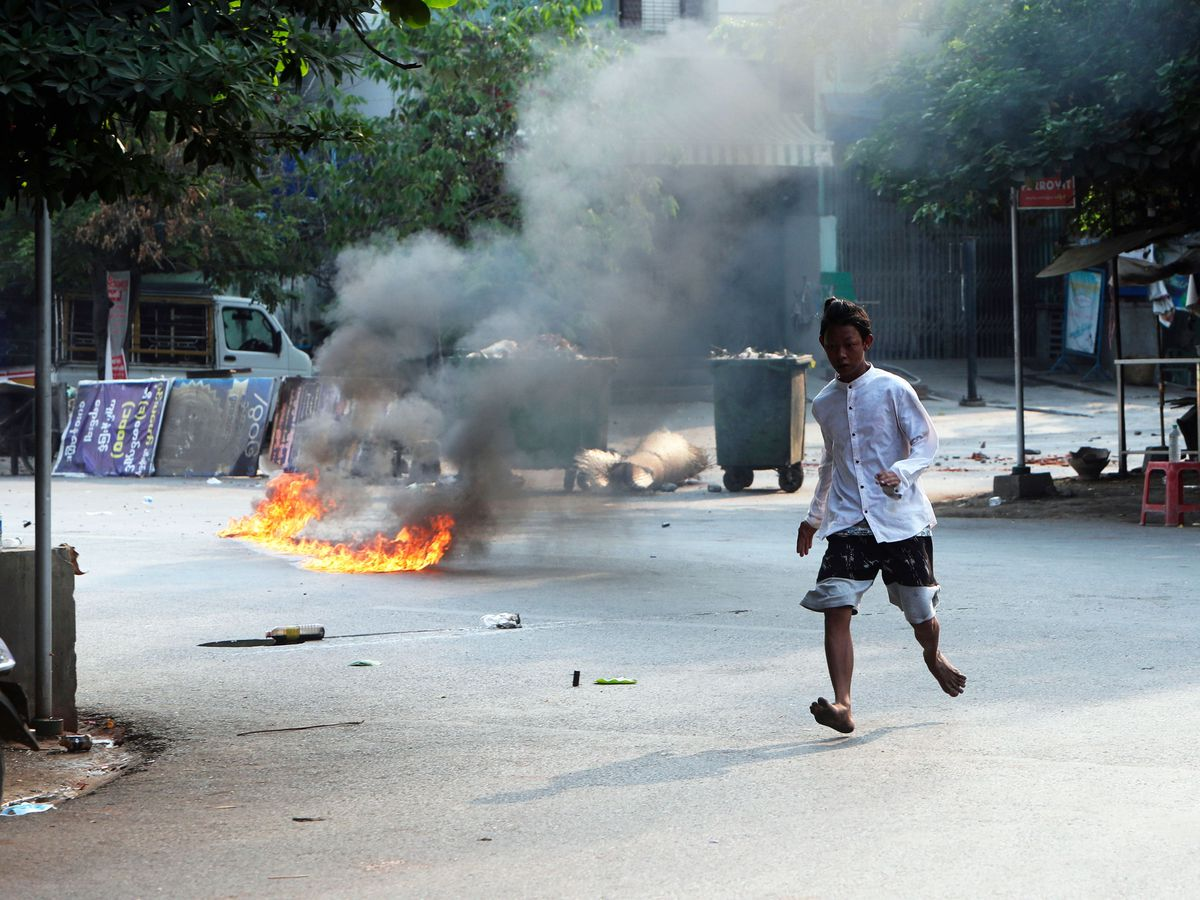 A man crosses the street while fire is seen in front of a road barricade that prevents security forces from advancing in Mandalay, Myanmar (AP)