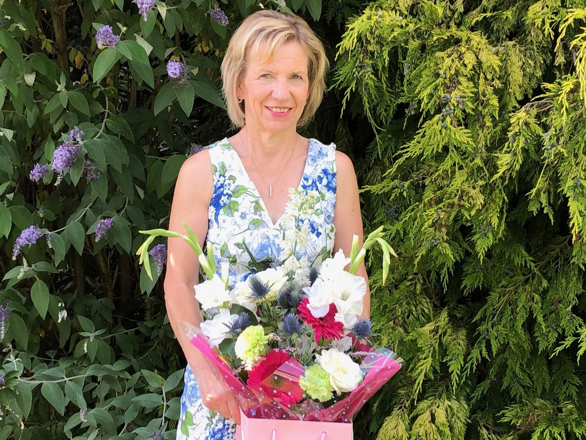 Gillian Newell in her garden with her delivery of flowers