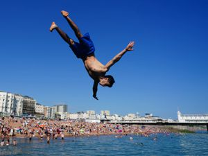 People jump into the sea from a groyne at Brighton beach