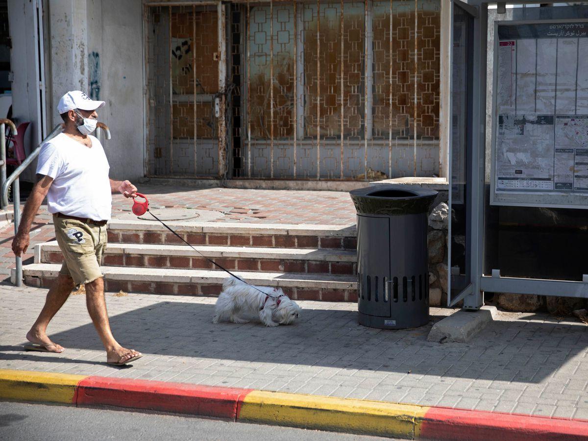 A man walks a dog near the talking bin