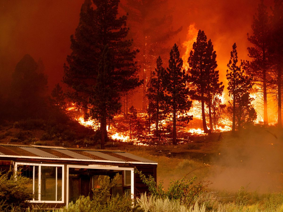 The Tamarack Fire burns behind a greenhouse in the Markleeville community of Alpine County, California
