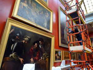 Collections assistant Holly Kirby carefully cleans the artwork in the picture gallery at Attingham Park mansion