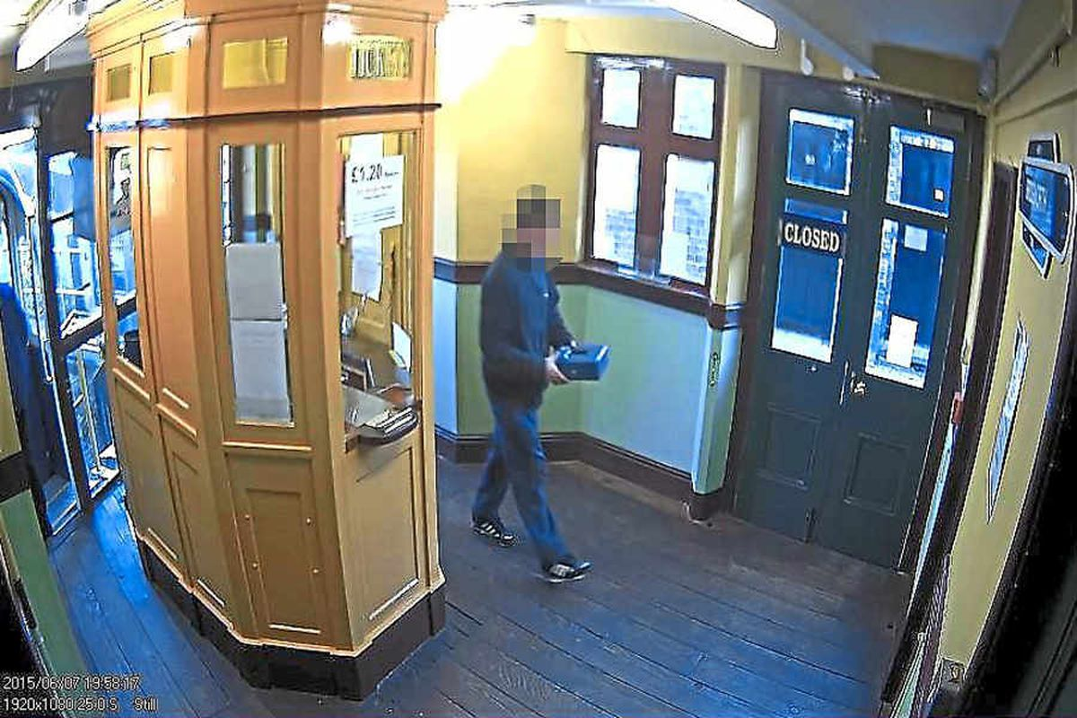 A man is seen taking away the blue cash box