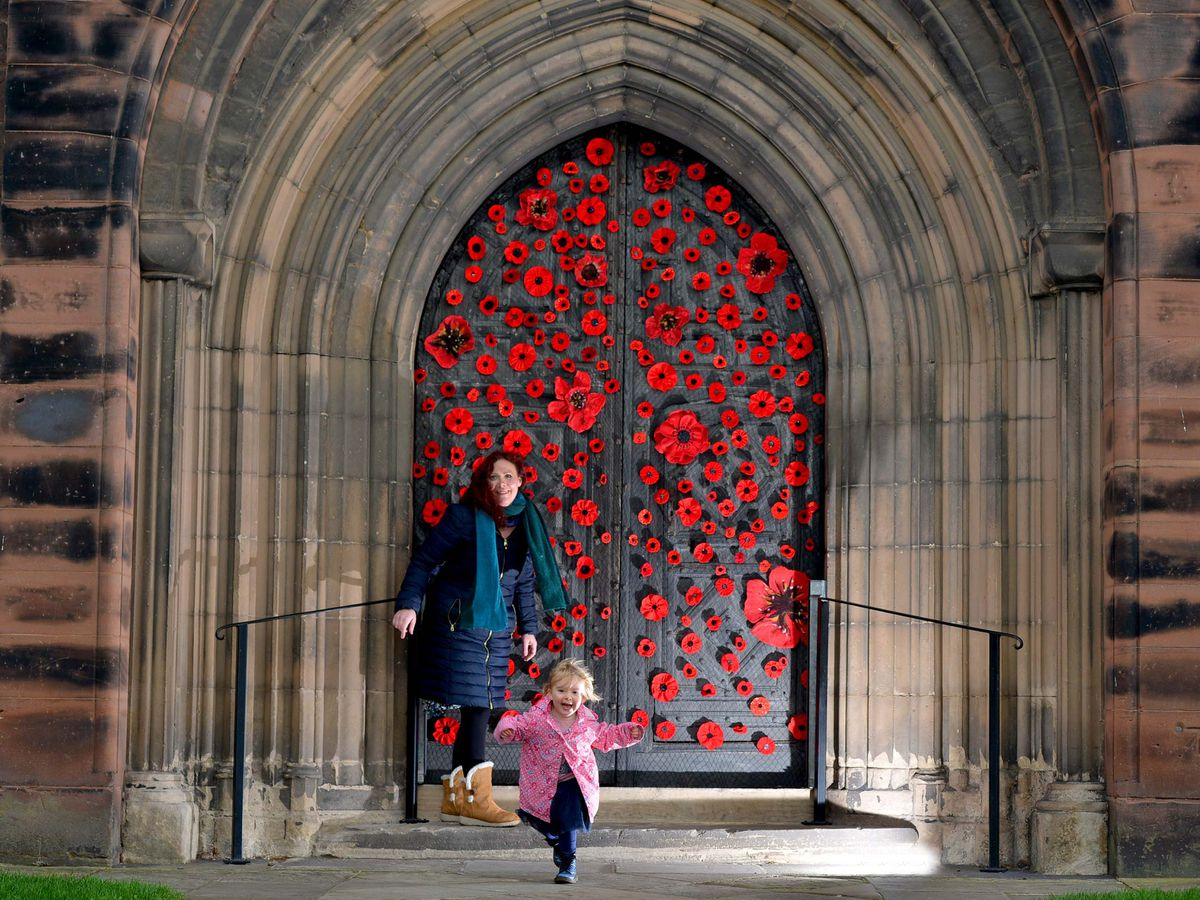 Isla Hunwick with her daughter Rose, aged two, outside the decorated Shrewsbury Abbey doors for Remembrance Day