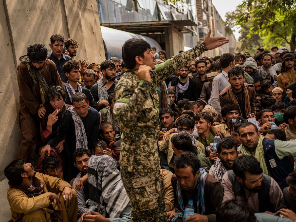 Afghans wait in front of a bank as they try to withdraw money in Kabul