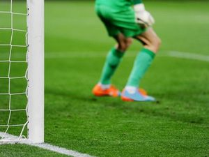 A goalkeeper waits in front of their goal