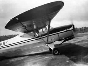 """A photo from David's collection showing a Terrier aircraft, registration G-AHST, being """"wound up"""" by one of the ground crew at the start of the day at Pendeford aerodrome."""