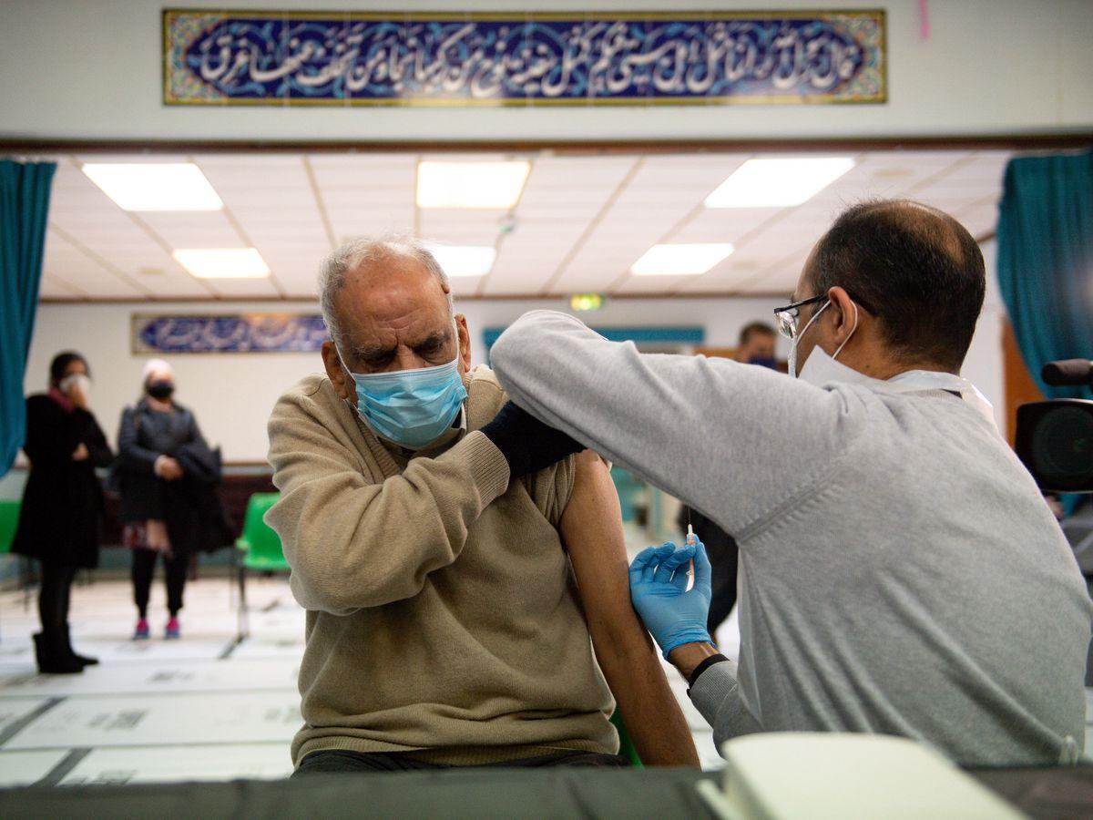 An elderly man receives a Covid jab