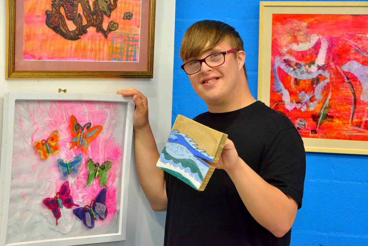 Thomas Shacklady 23 with some of his art and other students work.
