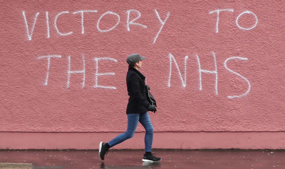 A woman walks past graffiti in support of NHS workers