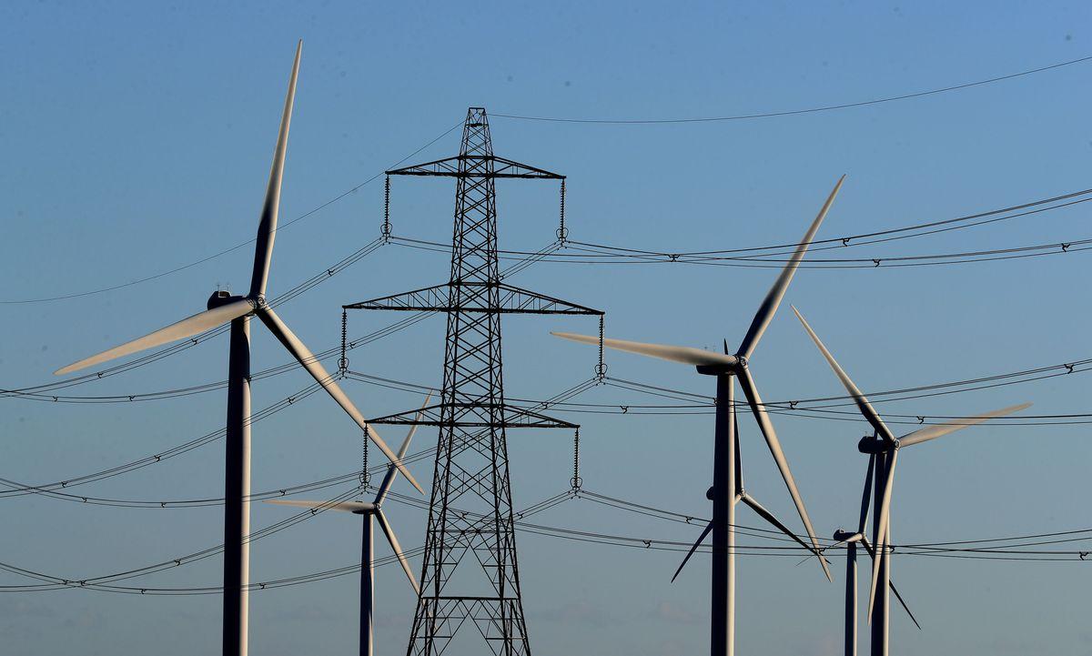 Wind farm amongst electricity pylons.