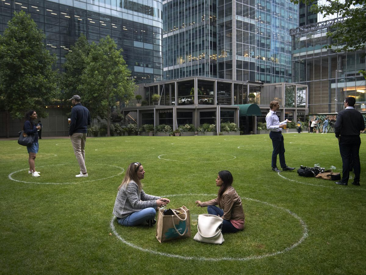 Drinkers stand within rings marked on the grass to maintain their social distance outside a bar in Canary Wharf, east London