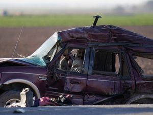 Law enforcement officers sort evidence and debris at the scene of a deadly crash in Holtville, California
