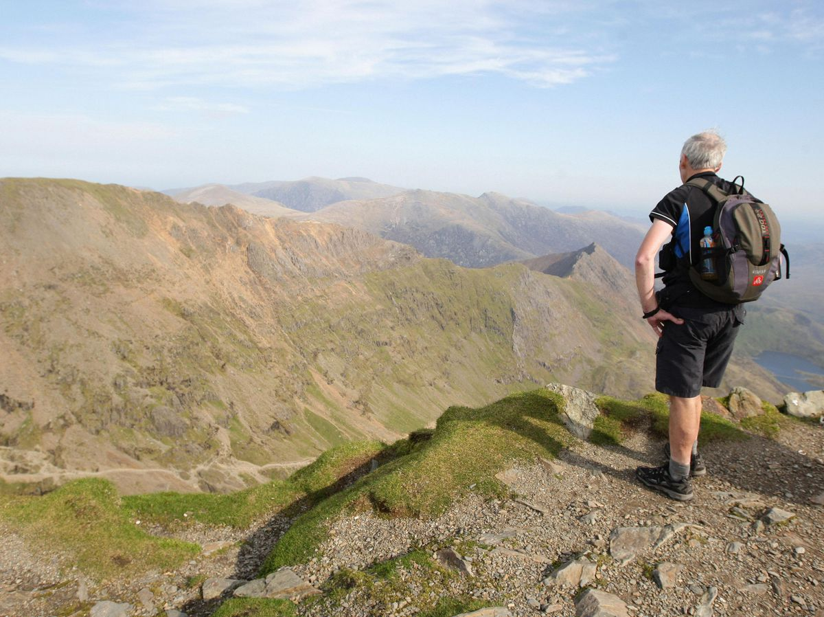 A walker looks out from the summit of Snowdon