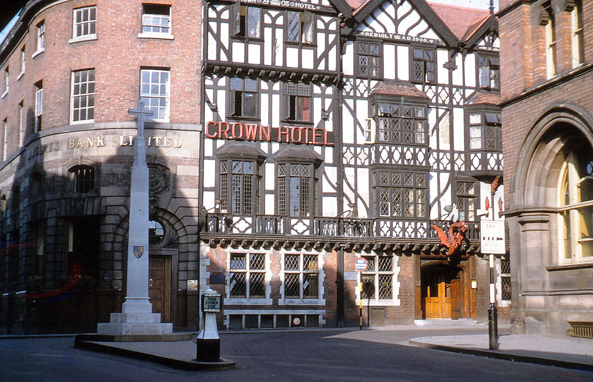 Today only the cross remains in this scene taken at the top of Pride Hill. Barclays Bank, on the left, was rebuilt in 1959. Shrewsbury post office, glimpsed to the right, was replaced in 1963. The Crown Hotel was demolished in 1962. The magnificent red dragon over the hotel's entrance was carved out of solid oak by a Russian emigre soon after the hotel opened.