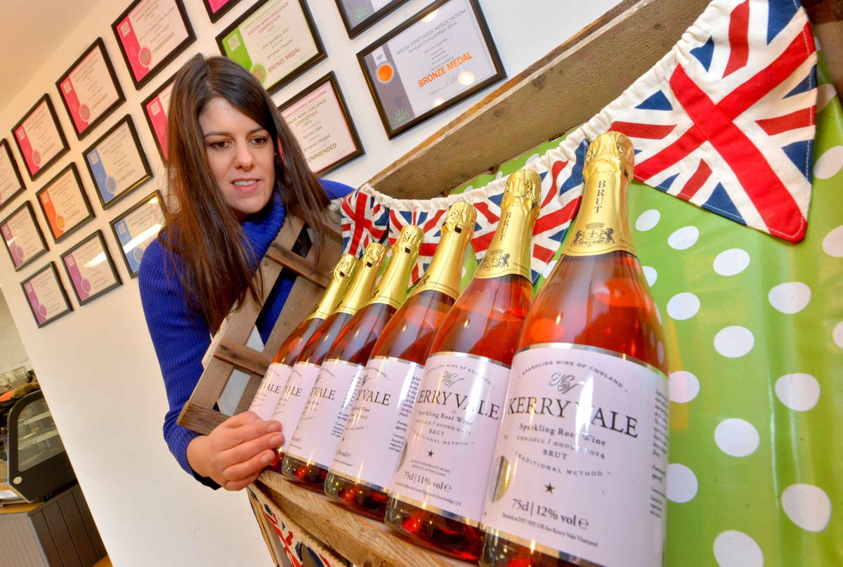 Nadine Roach with some of their rose sparkling wine on sale in their shop