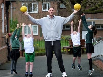 Britain's tallest man drops in on schoolchildren