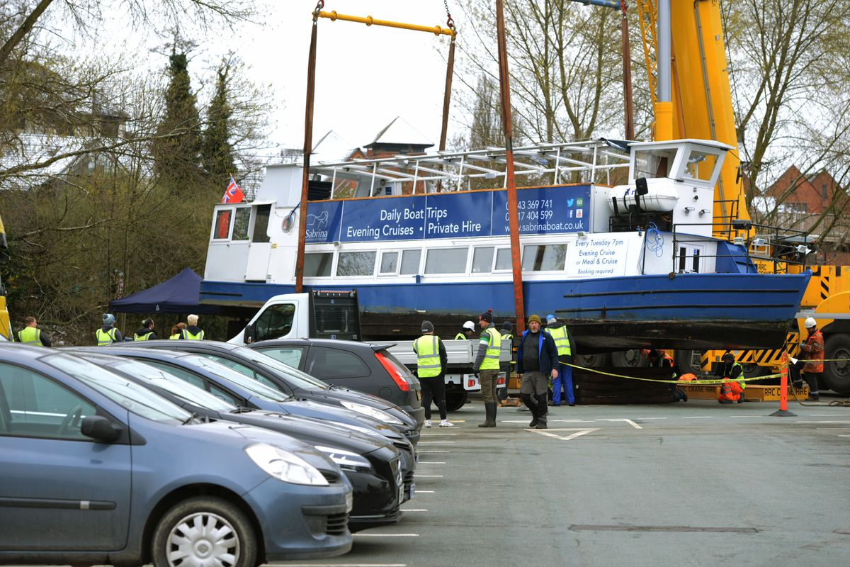 Inspectors checked underneath after the Sabrina was lifted from the River Severn by crane to dry dock on Frankwell car park