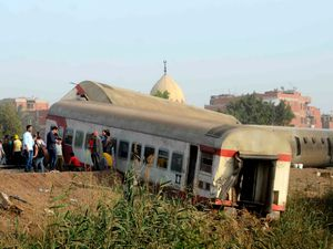 People gather at the site where a passenger train derailed injuring at least 100 people, near Banha, Qalyubia province, Egypt (Tarek Wagih/AP)