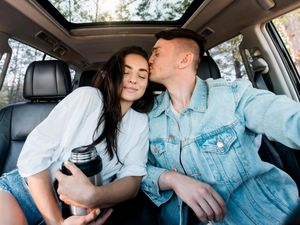 Man kissing woman in the car