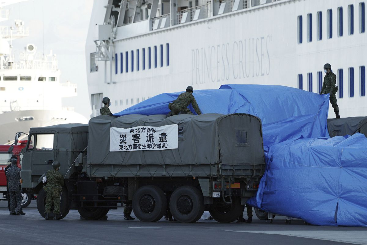 Members of the Japan Self Defence Forces prepare a supply truck to link up with the cruise ship Diamond Princess