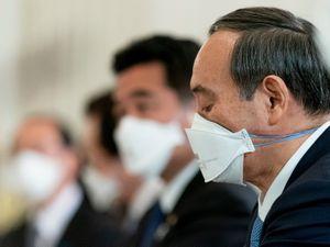 Yoshihide Sugar wears a mask
