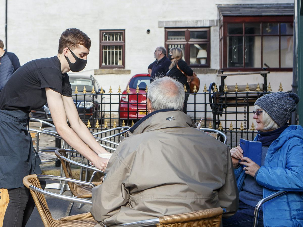 Customers sit outside a cafe in Haworth, West Yorkshire