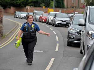 A PCSO helps manage the queue waiting to get into the Shell garage in Newport on Saturday