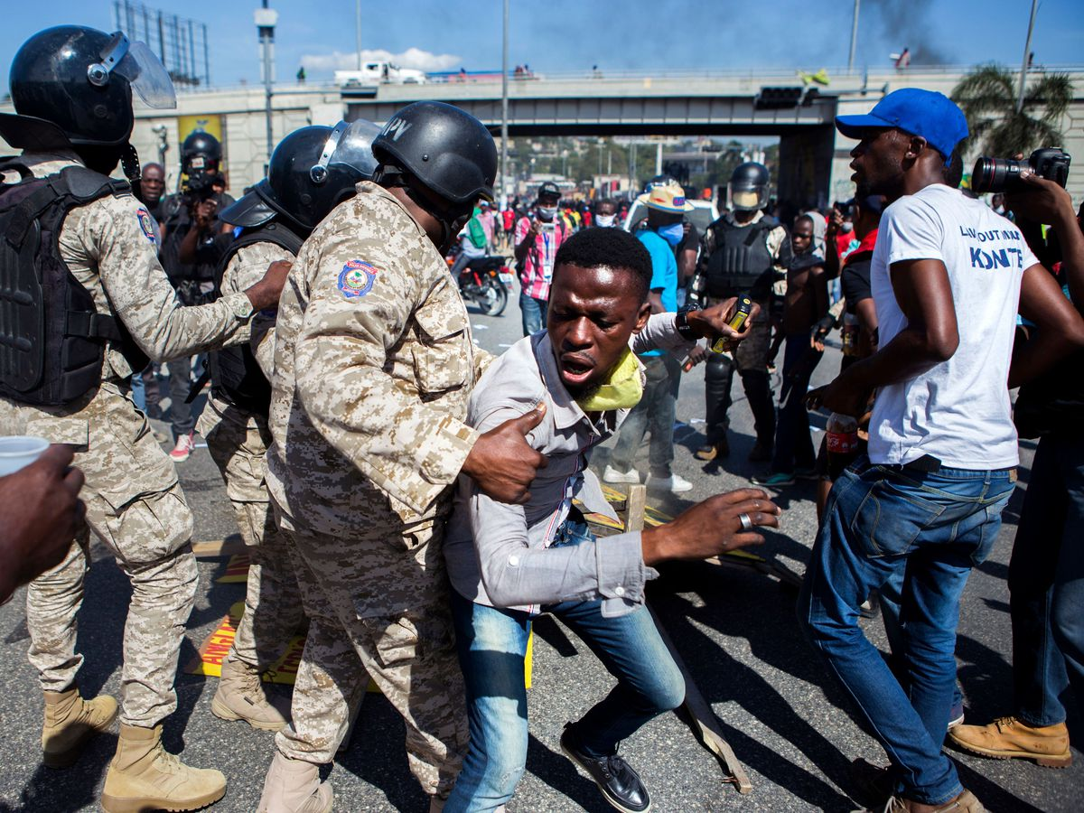 Police officers prevent a protester from fueling a burning barricade during a demonstration demanding the resignation of President Jovenel Moise, in Port-au- Prince, Haiti