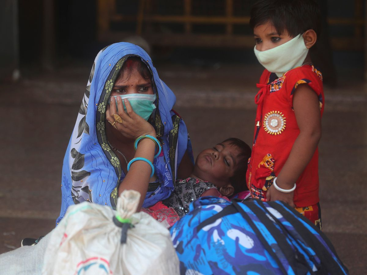 A woman and her children wait for a train at Lokmanya Tilak Terminus in Mumbai, India