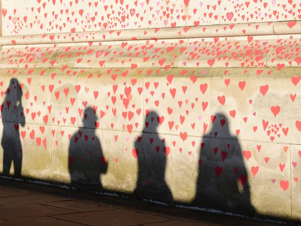 People are silhouetted against the COVID-19 Memorial Wall on the Embankment, central London (Ian West/PA)