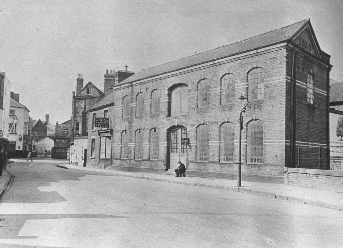 """We're in Smithfield Road, Shrewsbury, in 1938, and we can read some of the signs to tell us some of the features. The name on the end of the big building is """"Swain"""" and the man is sitting under a sign which says """"To Let."""" The hanging sign just left of centre says """"(first word unreadable) Advertising and Outdoor Publicity Office."""" Further along is a pub because there is a hanging sign for """"Border Ales"""" and written on what appears to be a gate or entrance at the head of the road is """"Withers."""" On the left corner of the junction is a hotel."""
