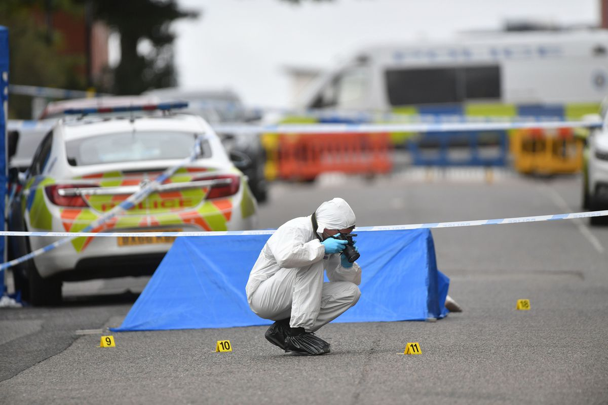 A police forensics officer taking photographs in Irving Street, Birmingham