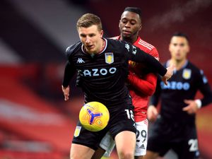 """Aston Villa's Matt Targett holds off Manchester United's Aaron Wan-Bissaka during the Premier League match at Old Trafford, Manchester. PA Photo. Picture date: Friday January 1, 2021. See PA story SOCCER Man Utd. Photo credit should read: Lindsey Parnaby/PA Wire RESTRICTIONS: EDITORIAL USE ONLY No use with unauthorised audio, video, data, fixture lists, club/league logos or """"live"""" services. Online in-match use limited to 120 images, no video emulation. No use in betting, games or single club/league/player publications.."""