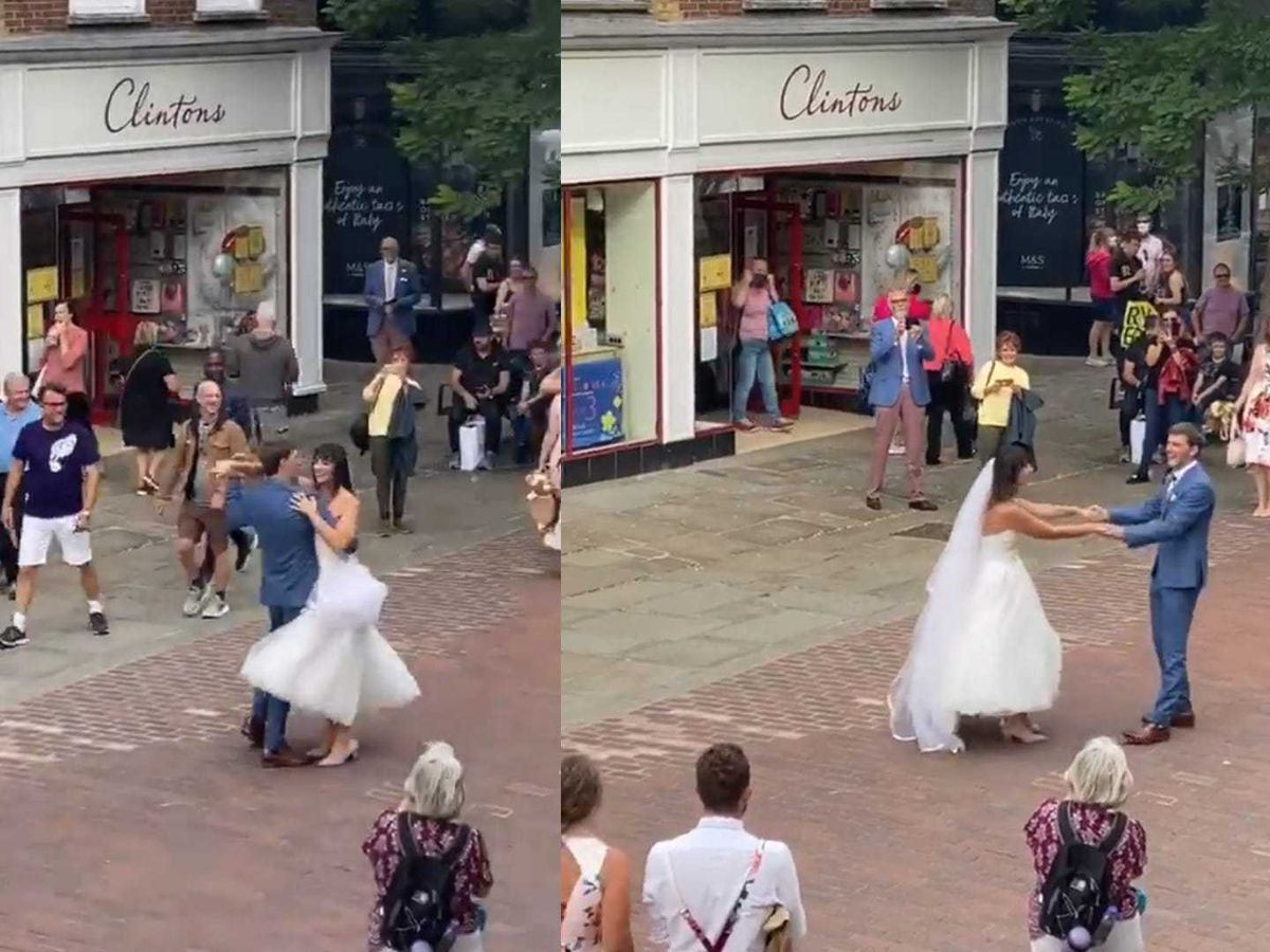 A married couple dance on the streets of Chichester as a busker plays on the guitar