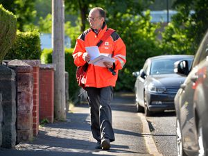 Postman Lee Sammons on his rounds in Heath Town