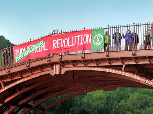 Climate change protestors tie a banner onto the Iron Bridge, in Ironbridge