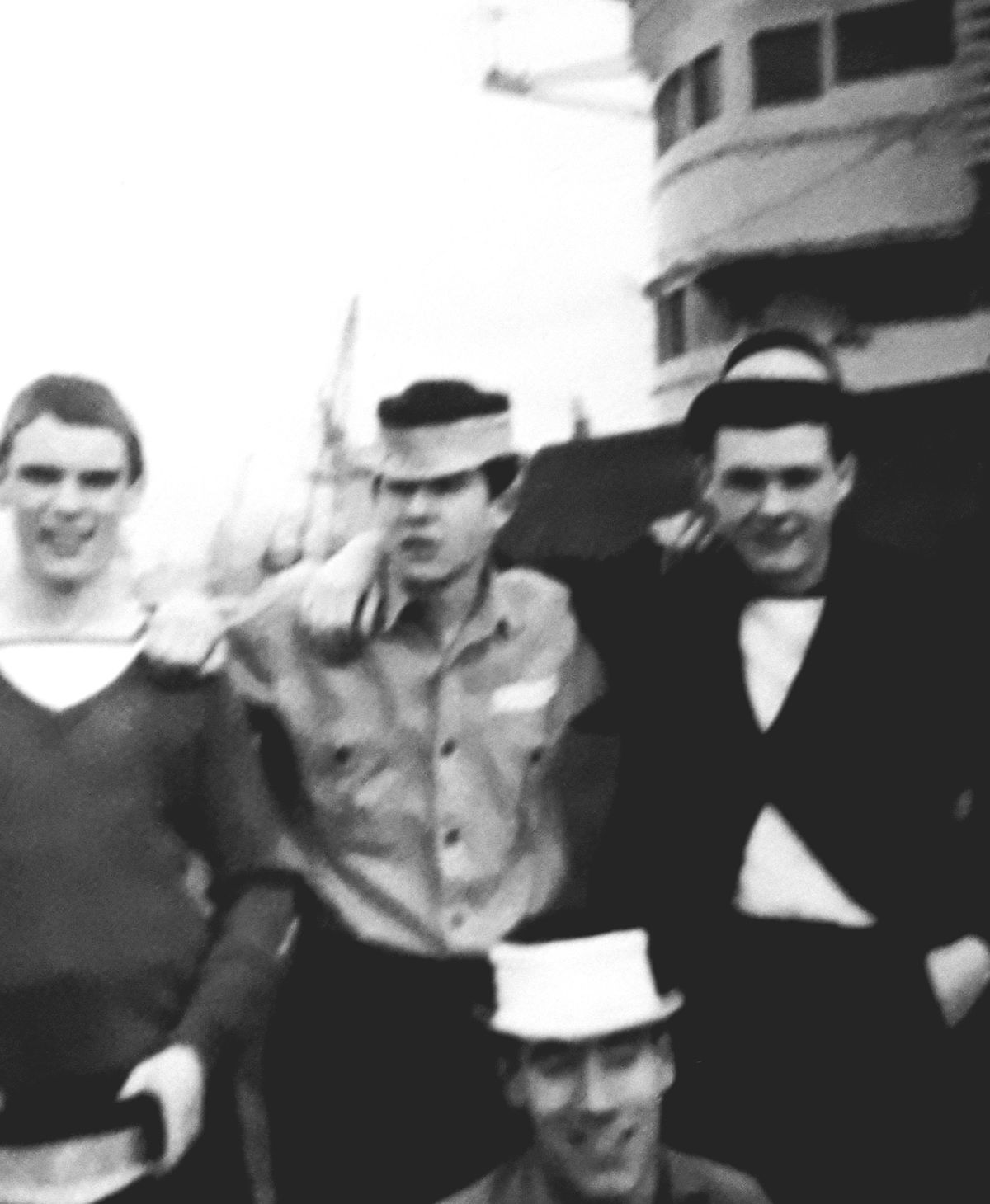 """John, standing centre, on HMS Victorious having """"adapted"""" his naval cap."""