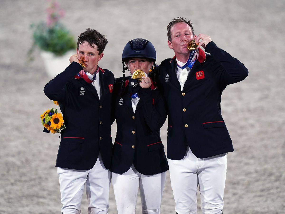 Tom McEwen (left) celebrates Olympic gold with Laura Collett and Oliver Townend